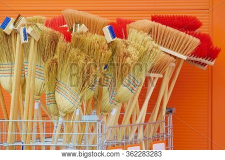 Stack Of New Diferent Brooms, Brushes And Besoms In Front Of Store