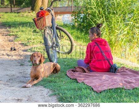 Nyiregyhaza, Hungary. June 29, 2019: Young Modern Girl With Magyar Vizsla Dog Relaxing On The Lake.