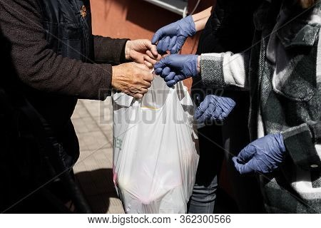 Young People Helping Old Woman With Products. Hands In Gloves, Help During Quarantine  Through Coron