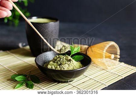 Organic Green Matcha Tea And Tea Accessories On Japanese Mat On Black Background. Japanese Tea Cerem