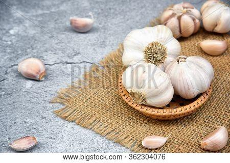 Organic Garlic. Fresh Garlic Cloves And Garlic Bulb In Wooden Basket On Dark Background With Pile Of