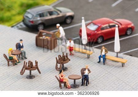 Social Distancing Rules With Miniature People At A Sidewalk Cafe