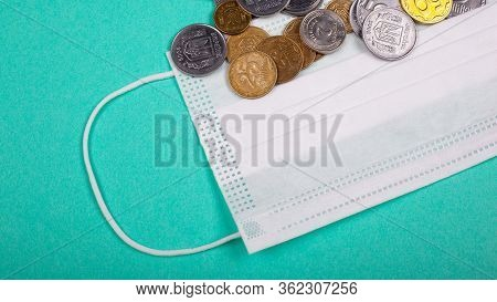 Rising Prices For Medical Masks, Protective Mask And A Handful Of Coins On A Blue Background. Rise I