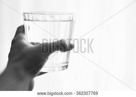 Full Glass Of Water In A Female Hand On A White Background, Place For Text, Bw Photo.