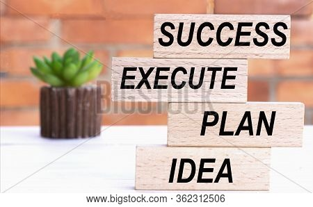 Idea, Plan, Execute, Success The Words On Cubes Against The Background Of A Brick Wall With A Cactus