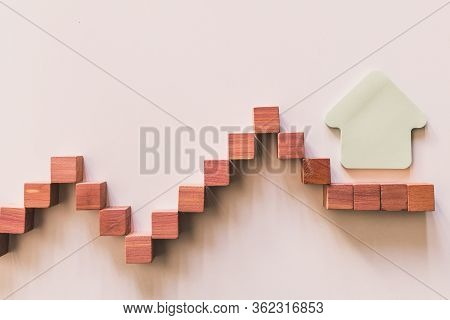 Graphic Curve Made With Wooden Boxes With House Shape On The End. House Budgeting