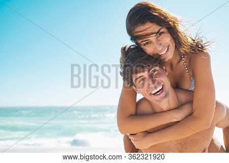 Happy couple in love enjoy summer vacation at beach with copy space. Man giving piggyback ride to his beautiful girlfriend while looking at camera with sea in background. Couple having fun at beach.
