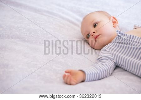 Portrait of a six months old baby boy lying on bed with copy space. Cute little boy looking away. Adorable toddler wearing white and light blue striped body in bedroom.
