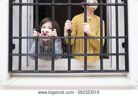 Two Confined Children Stay Behind Their Home Bars Window. The Boy Looks Accusingly To The Camera