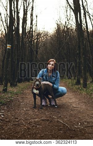 Attractive And Pretty Brunette Girl (female) Posing With Her Guardian Dog On A Road In A Spring Time