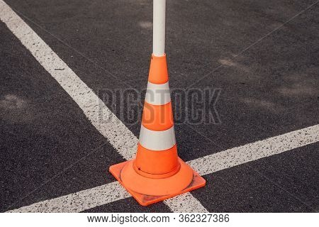 Traffic Cone At The Intersection Of The White Lines Of Road Markings. Symbol Of Restrictions, Road W