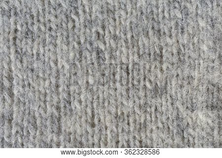 Close-up Of Knitted Gray Woolen Texture. Knitted Fabrics. Background Of A Knitted Fabrics.