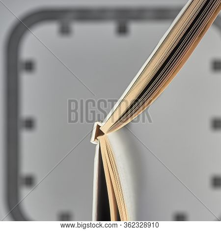 An Open Book Is Like The Hands Of A Clock On The Background Of Dial In Blur. Open Book And Clock Fac