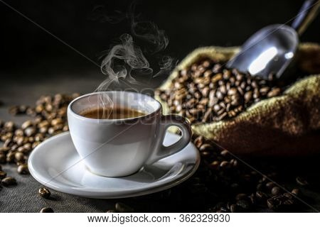 cup with steaming Italian coffee, jute sack with roasted coffee beans. concept of hot drinks, breakfast, break.