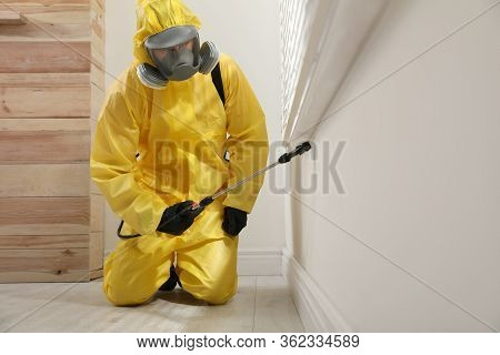 Pest Control Worker In Protective Suit Spraying Insecticide On Window Sill At Home