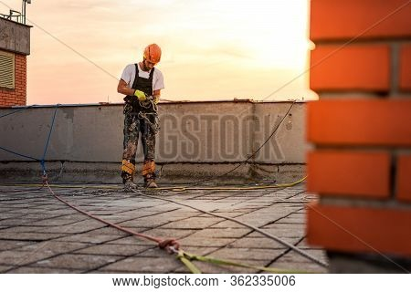 Industrial Climber Hanging On The Rope While Painting The Exterior Facade Wall Of The Tall Apartment
