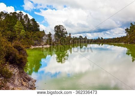 Wai-O-Tapu Geyser Park. Cumulus clouds are picturesquely reflected in the smooth surface of hot water. New Zealand, North Island. The concept of exotic, ecological and photo tourism