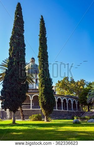 The Catholic Church of the Italian female Franciscan monastery on Mount Bliss in the Galilee. Flock of migratory birds flies. High shore of Lake Tiberias. The concept of religious pilgrimage tourism