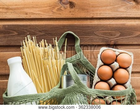 Food Donation Cotton Mesh Bag With Pasta, A Can Of Canned Food, A Bottle Of Milk, Eggs On Wooden Bac