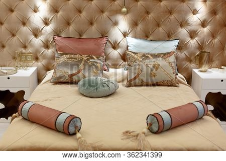 Seven Pillows Of Different Colors Lie On The Bed. Rectangular And Round Pillows In Beige Colors. The