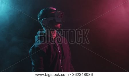Portrait of a man in virtual reality helmet. Obscured dark face in VR goggles. Internet, darknet, gaming and cyber simulation.