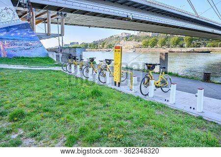 Bratislava (slovakia) - April 20 2020: Yellow Public Bikes Locked In Docking Station On Bank Of Danu