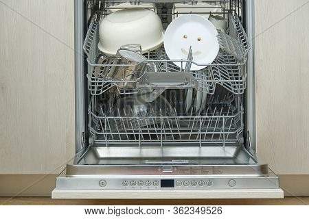Fine Washed Dishes In The Dishwasher. Integrated Dishwasher With White Plates Front Vew And Happy Em