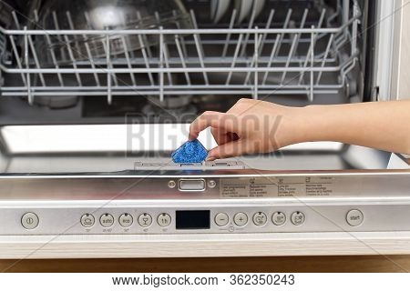 Putting Tab Into Integrated Dishwasher Close Up. Dishwasher Machine Full Loaded. Woman Hand Holding