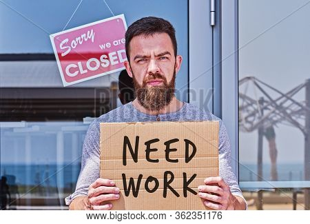 Unemployed Guy With Signboad Need Work Near Closed Door Office Or Cafe. Unemployment During Coronavi