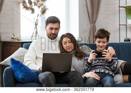 Mother, Father And Son Using Laptop And Mobile Phones At Home. Family Members Ignoring Each Other An