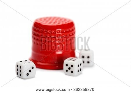 Thimble and miniature dice isolated on white