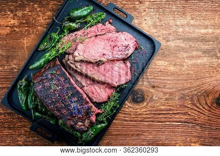 Traditional Commonwealth Sunday roast with sliced cold cuts roast beef with herbs and chili as top view on a modern design tray with copy space right