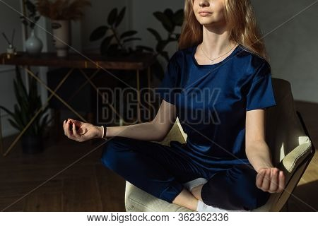 Young Woman Meditating In Armchair At Home. Young Women Meditating With Mudra Sign At Yoga Class Or