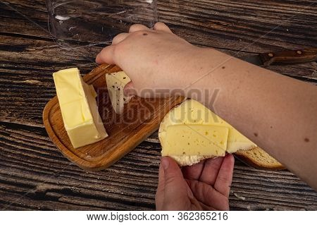 Someone Puts A Slice Of Cheese On Fresh Wheat Toast With Butter And A Piece Of Butter In A Wooden Bu