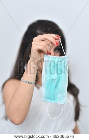 Girl Holds A Medical Mask On A Light Background. The Girl Is Holding A Mask. Medical Mask And A Beau