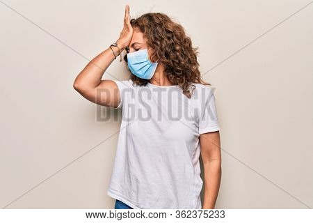 Middle age woman wearing coronavirus protection mask for covid-19 epidemic virus surprised with hand on head for mistake, remember error. Forgot, bad memory concept.