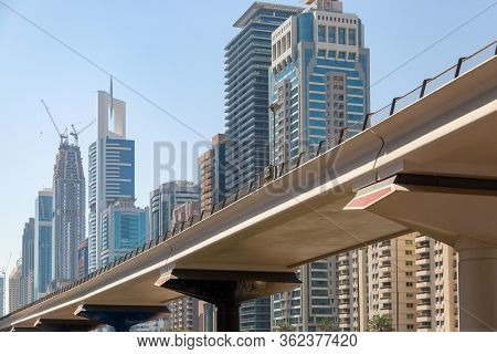 Automobile Bridge On The Background Of Tall Buildings. Flyover Over The Road Against The Blue Sky An