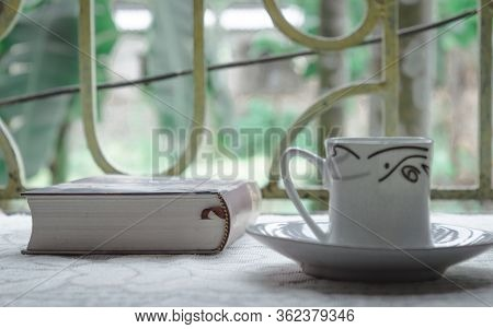 A Cup Of Coffee And A Book On Window Sunlight In Morning. Time To Finish A Novel To Discover Somethi