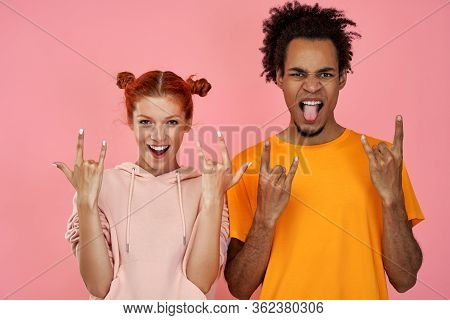 Photo Of Punky Joyful Black Man And Ginger Woman Hear Music Of Favourite Band, Show Rock N Roll Gest