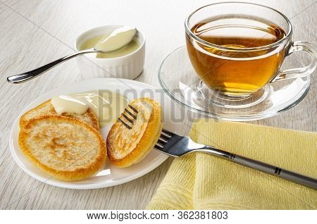 Teaspoon In Bowl With Condensed Milk, Transparent Cup With Tea On Saucer, Pancake Strung On Fork, Pa