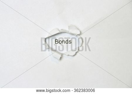 Word Bonds On White Isolated Background, The Inscription Through The Wound Hole In The Paper. Stock