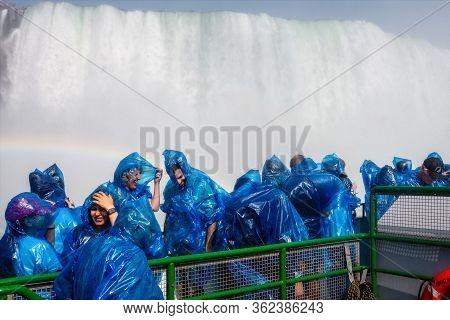 Niagara Falls, Ny, Usa - June 12, 2019: Happy Visitors In Raincoats On A Tour Boat Under The Splashe