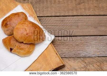 Russian Pirozhki (baked Patties) With Berries On Wooden Cutboard On Wooden Background
