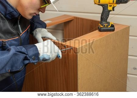 Furniture Maker Assembling Furniture With Screwdriver. Assembly Of Furniture