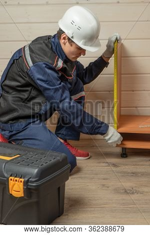 Young Man Dressed In Workers' Overall Assembling Furniture Sitting On The Floor. Assembly Of Furnitu