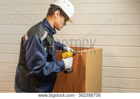 The Repairer In Assembly Of Furniture Collects New Furniture. Young Repairman Assembling New Table A