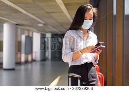 Young Asian Tourist Woman With Mask Using Phone And Holding Passport At The Airport
