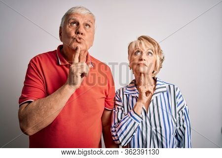 Senior beautiful couple standing together over isolated white background Thinking concentrated about doubt with finger on chin and looking up wondering