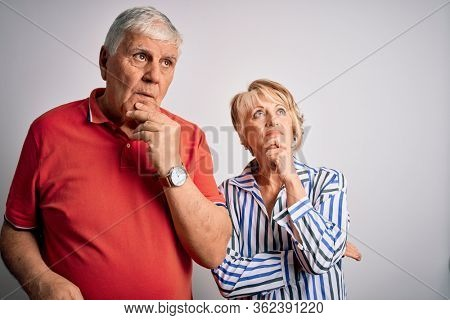 Senior beautiful couple standing together over isolated white background with hand on chin thinking about question, pensive expression. Smiling with thoughtful face. Doubt concept.