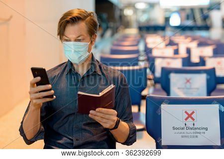 Young Tourist Man With Mask Checking Phone And Passport While Sitting With Distance At The Airport